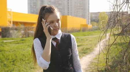 adolescência : Schoolgirl comes home from school. Girl teenager talks to his mom on the phone on the way home.
