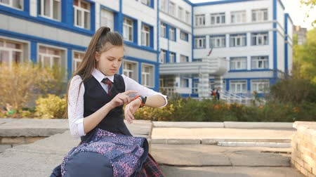 браслет : Teenager girl sitting on the parapet near the College with a backpack and looking at his smart watch.