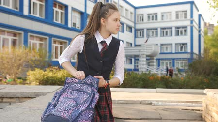 pedometer : Teenager girl on break in the courtyard of the College sits on the parapet with a backpack and sets the alarm on the smart watch. Stock Footage