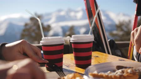 vin brulè : Couple of skiers drinking mulled wine on the mountain at lunch time. Close-up cups with mulled wine on the sky background.