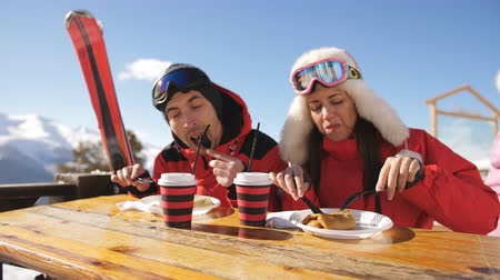 mulled wine : Couple of skiers on the mountain having lunch in restaurant outdoors. The ski resort. Stock Footage