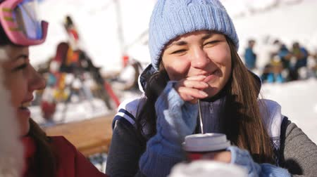 mulled wine : Two cute girl skier sitting in a cafe on top of the mountain drinking mulled wine and fun talk. Stock Footage