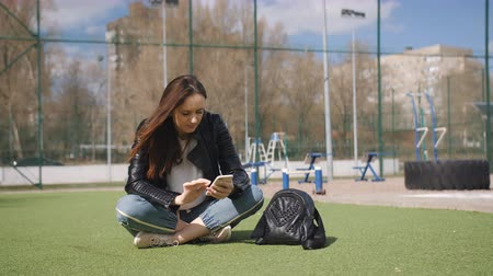 колледж : Young woman use of mobile phone and sitting on green lawn