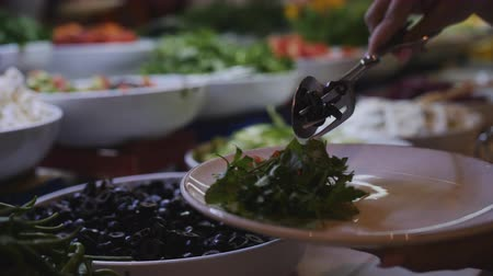 ovoce a zelenina : A woman puts a plate of olives from the buffet in the hotel restaurant, close-up.
