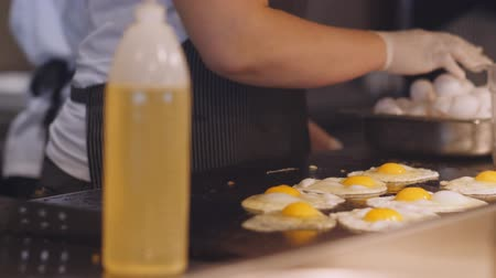 frypan : Woman cook in the kitchen frying a lot of eggs on a metal plate. Cooking Breakfast in the kitchen.