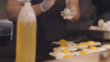 frypan : Woman breaks the eggs and pours them on a metal hot plate. Stock Footage