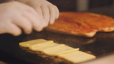 taje : Cook decomposes on a hot metal plate the slices of cheese. Preparing sandwiches in the kitchen for Breakfast.