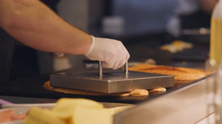 cheese slices : The chef toasts the buns on the grill plate for making sandwiches.