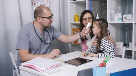 medical thermometer : Friendly doctor talks with patients mom and her daughter. The doctor measures the temperature of the little girl in his office.