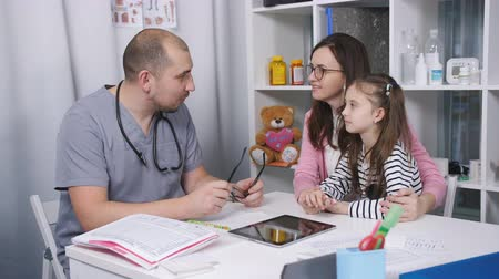 md : Friendly doctor talks with patients mom and her daughter. The doctor in her office examines a sore throat of a little girl. Stock Footage