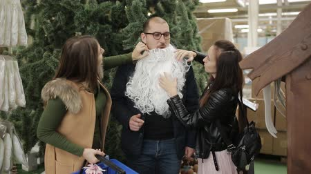 мишура : Friends having fun on sale Christmas decorations. Friends try on the beard of Santa. Стоковые видеозаписи