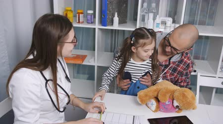 увеличилась : Father-daughter time in the office of a pediatrician. Female doctor measures the temperature of a small girl.