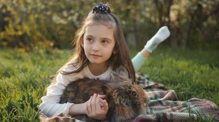 cheirando : Little girl hugging and stroking a fluffy brown rabbit on green grass.