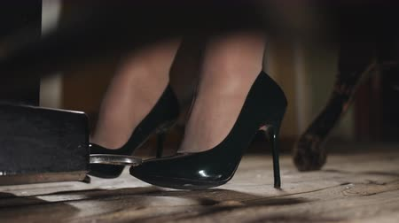 スタッド : A woman plays piano in the concert hall. Close-up of feet in shoes heels pressing on the pedal. 動画素材