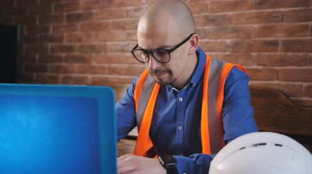 hardhat : Close-up of a young architect wearing a beard and glasses and works on a laptop over a new architectural project Stock Footage