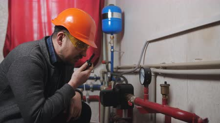 boru hattı : The engineer in the boiler room pressure monitors and checks the efficiency of equipment. The engineer reports on the radio performance of the equipment.