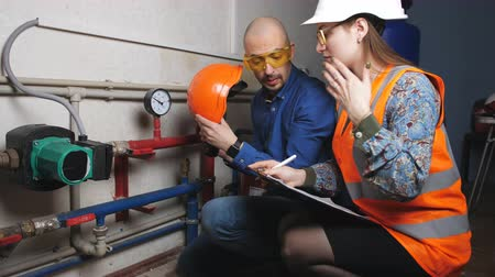heating system : Female reviewers and male engineer in a protective helmet inspect pipe compartment on the subject of correct operation to all nodes. Stock Footage