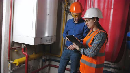 termostat : Male engineer and a female checker check operability of equipment in the boiler room. The woman enters the data into technical documentation. Wideo
