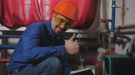 termostat : Portrait of an engineer in the boiler room near the pipe and sensors. A man in a hardhat smiling and looking at the camera. Wideo