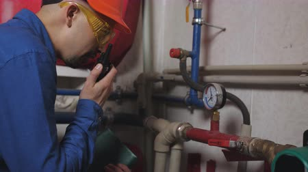 termostat : Engineer in a protective helmet and goggles and inspected the gas boiler in the tube compartment.