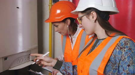 termostat : Two woman engineers checking technical data of heating system equipment in a boiler room