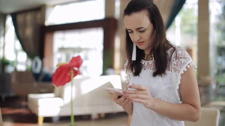 business style : Beautiful woman using a tablet in a hotel lobby sitting enjoying a cup of coffee on an ornate couch smiling as she reads the screen Stock Footage