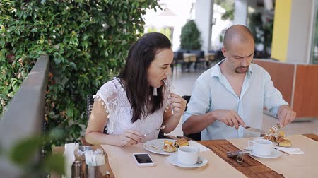huevos revueltos : Young couple eating and talking during breakfast by table in the outdoor cafe