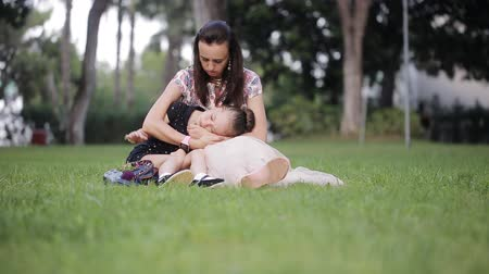 crying baby : Mother with a crying daughter sitting on the grass and mom comforting daughter
