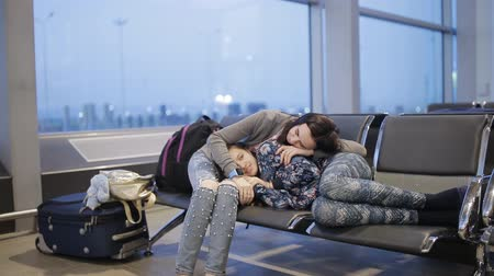 lugares sentados : A woman with her daughter at the airport in the waiting room, spend the night and wait for flight
