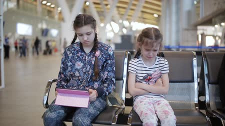 pasaport : Two sisters at the airport. Little girl upset with her sister because tablet.
