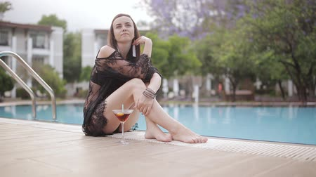 ninhada : Sexy woman in swimsuit sitting thoughtfully on the edge of the pool with a Martini