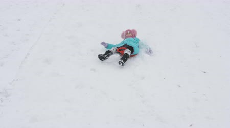 toboggan : Girl rolls down hill in sleigh in snow. girl plays in winter in park. Slow motion