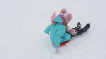 recreational park : A child in winter rolls down the hill. The little girl is on an ice. Slow motion.