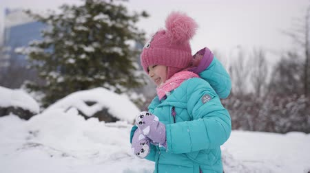 śnieżka : The little girl in the Park in the winter dad throws snowballs out of hiding.