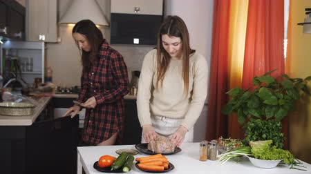 благодарение : Two girls talk fun in the kitchen and prepare a delicious dinner. Two friend in the kitchen preparing the chicken baked in the oven.