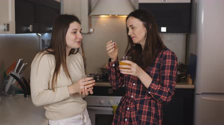 питательные вещества : Two girlfriends in the kitchen drinking orange juice out of glasses and communicate. Стоковые видеозаписи
