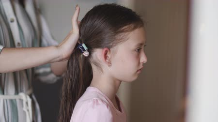 fonat : Mom braids little girl in front of a mirror.