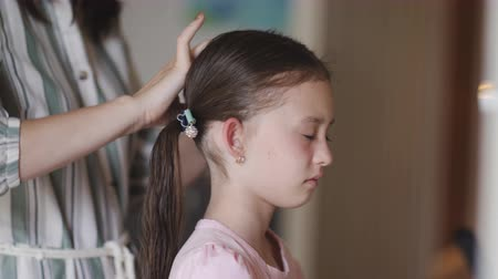 косички : Mom braids unhappy little girl in front of a mirror.