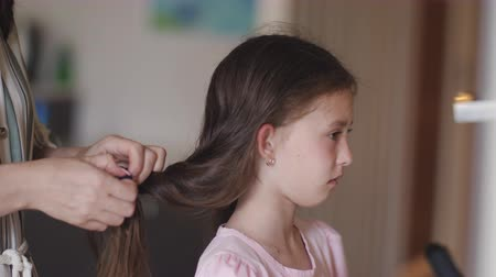 pigtail : Mom braids and comb a little upset daughter.