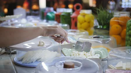 фета : Close-up of female hands placed on the plate of cheese from the buffet. Breakfast at the hotel. Стоковые видеозаписи
