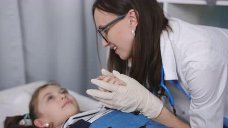 childrens : Smiling friendly female doctor talking with little patient lying on a hospital bed in the pediatricians office