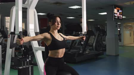 construção muscular : Sports girl does exercises on a strength trainer at the gym.