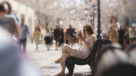 почтовый : Young beautiful woman using a smartphone sitting on bench on the street in the city centre, in the background, and the foreground people walking and going about their business.