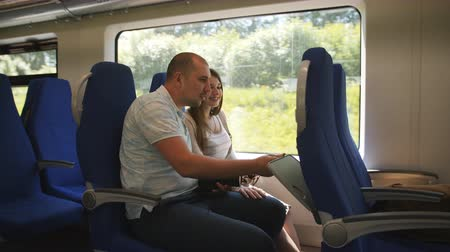 přihrádka : A couple in love traveling in the elektro train looking through the window at the surroundings.