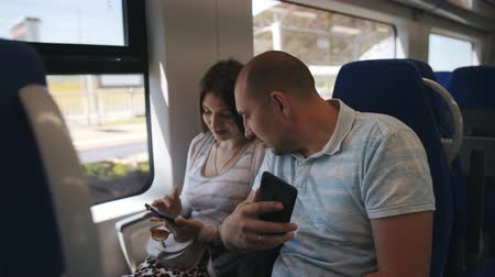 rekesz : A couple in love sitting in comfortable chairs looking at the photos on the smartphone. A couple in love traveling in the elektro train looking through the window at the surroundings. Stock mozgókép