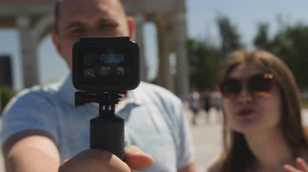 Couple of tourists in the city travel blog shoot action camera, close-up. Stok Video
