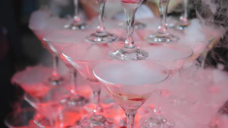 martinis : The pyramid of glasses with champagne and dry ice at the festival in slow motion. Stock Footage