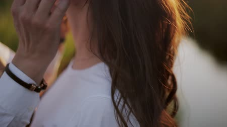 parte : Mans hand touches the hair of his beloved. Close up Romantic couple in love kissing outdoor at bright sunny day.