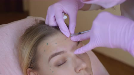 penetrating : Woman in healthcare clinic. Beauty injection procedure. Close up of cosmetologist holding a syringe with cannula needle penetrating female face. Stock Footage