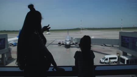 jitters : Silhouettes of two sisters in the lobby of the airport stand by the window and watching the planes on the runway.